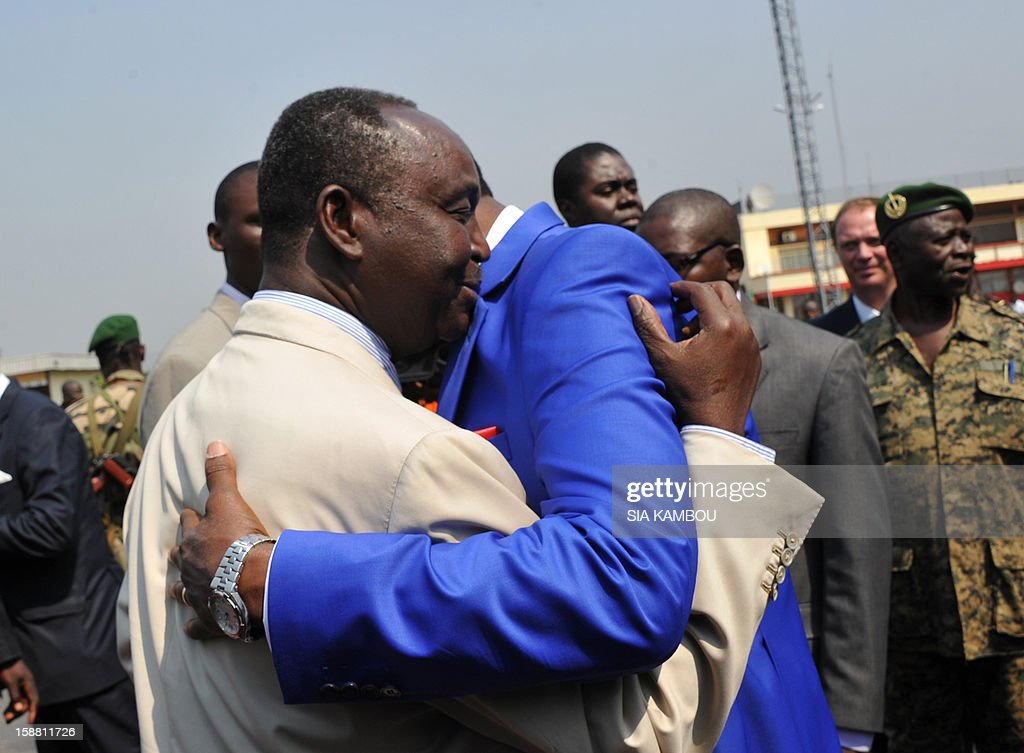The President of the Central African Republic, Francois Bozize (L), greets the current president of the African Union and President of Benin Yayi Boni (R), after the latter arrived at the airport in Bangui on December 30, 2012, for talks over the current crisis. Rebels in the Central African Republic who have advanced towards the capital Bangui warned they could enter the city even as the head of the African Union prepared to launch peace negotiations. Central African President Francois Bozize also stated today he was open to a national unity government after talks with rebel leaders and that he would not run for president in 2016. AFP PHOTO/ SIA KAMBOU