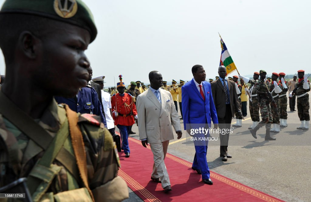 The President of the Central African Republic, Francois Bozize (Center L), walks alongside the current president of the African Union and President of Benin Yayi Boni (Center R), after the latter arrived at the airport in Bangui on December 30, 2012, for talks over the current crisis. Rebels in the Central African Republic who have advanced towards the capital Bangui warned they could enter the city even as the head of the African Union prepared to launch peace negotiations. Central African President Francois Bozize also stated today he was open to a national unity government after talks with rebel leaders and that he would not run for president in 2016. AFP PHOTO/ SIA KAMBOU