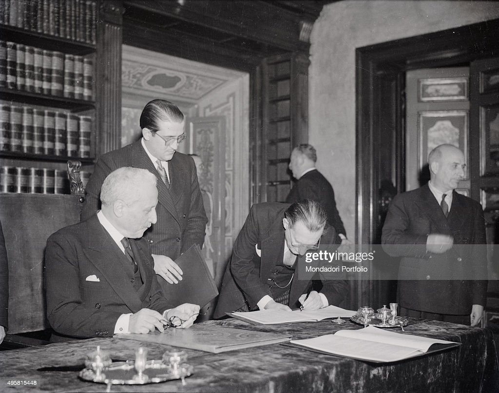 The President of the Council of Ministers of the Italian Republic Alcide De Gasperi signing the Constitution of the Italian Republic under the eyes...