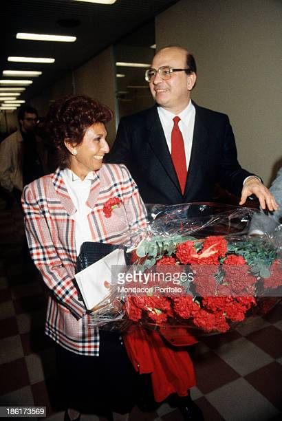 The President of the Council of Ministers of the Italian Republic Bettino Craxi smiling beside his wife Anna Moncini holding a bunch of carnations...