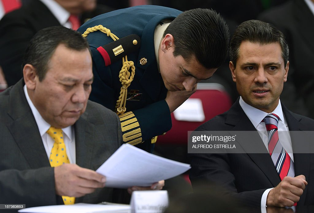 the President of the Democratic Revolution Party (PRD), Jesus Zambrano (L), reads a document next to Mexican President Enrique Pena Nieto (R) as they make the 'Pact for Mexico', on December 2, 2012 in Mexico City. Pena Nieto and the main three polical parties of Mexico, signed Sunday an agreement to launch reforms to strengthen democracy, fight social inequality and promote economical growth. AFP PHOTO/Alfredo Estrella