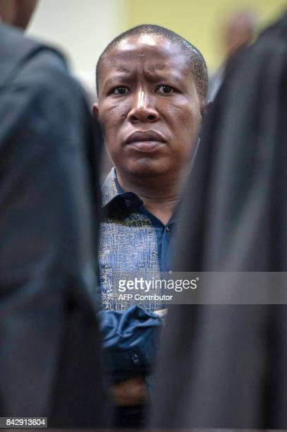 The president of the Economic Freedom Fighters Julius Malema talks with lawyers during a hearing brought by opposition parties seeking an order to...