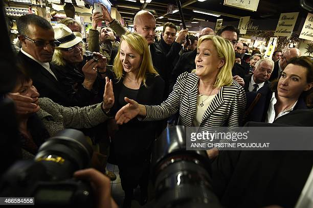 The president of the farright National Front party Marine Le Pen works the crowd on March 17 2015 with FN Vaucluse deputy Marion Marechal Le Pen at...