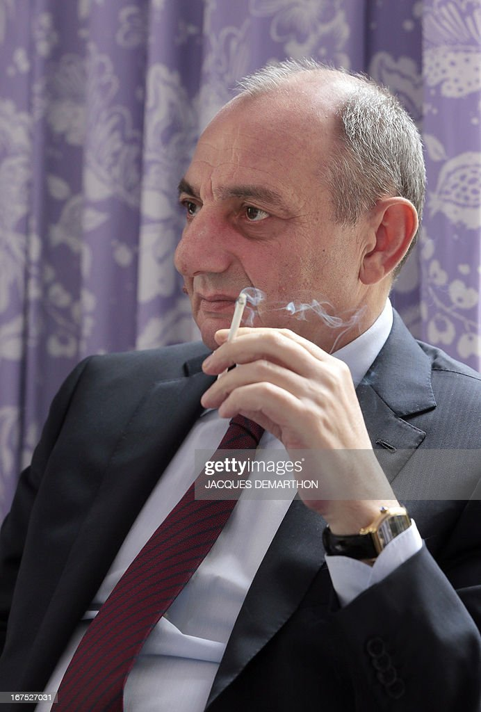 The president of the Nagorny Karabakh region's unrecognised government, Bako Sahakian, smokes a cigarette during an interview on April 26, 2013 during his three-day visit in Paris. The international community must take Azerbaijan's threats of regaining the disputed region of Nagorny Karabakh seriously and condemn Baku's ongoing arms-buying spree, the breakaway territory's leader said Friday. AFP PHOTO / JACQUES DEMARTHON