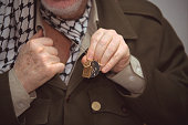 The President of the Palestinian authority shows the medals he wears around his neck in his office