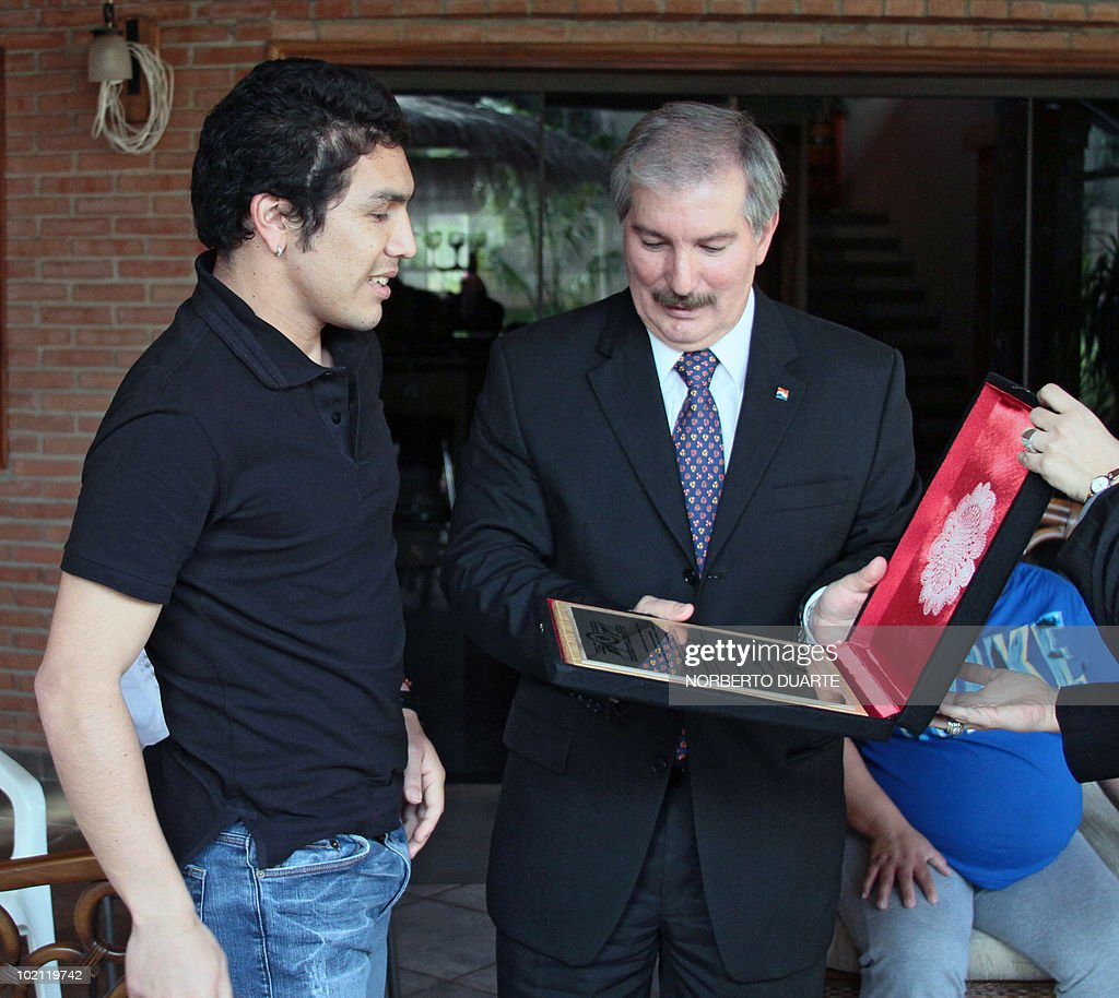 The president of the Paraguayan national Congress, Miguel Carrizoza (R), gives a recognition plaque to Paraguayan national football team player Salvador Cabanas on June 15, 2010 in Asuncion. Cabanas was seriously injured when he was shot past January 25 in a bar in Mexico City. AFP PHOTO / Norberto Duarte