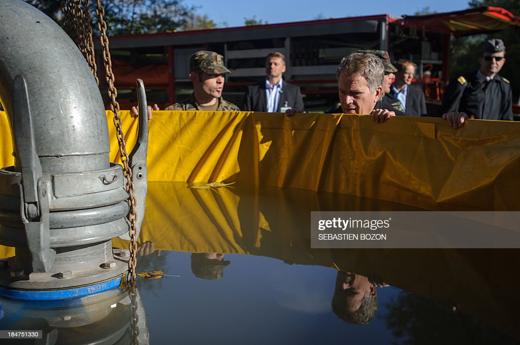 The President of the Republic of Finland, Mr Sauli Niinisto (R), looks at a tank for firemen as he visits the rescue troops at a Swiss military base on October 16, 2013 in Bremgarten.