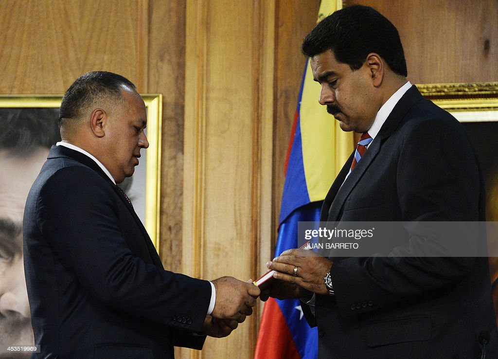 The president of the Venezuelan National Assembly, Diosdado Cabello (L), gives Venezuelan President Nicolas Maduro (R) the new law 'Plan de la Patria'--presented by the late president Hugo Chavez during the 2012 presidential campaign-- at the Miraflores presidential palace, in Caracas on December 4, 2013. AFP PHOTO/JUAN BARRETO