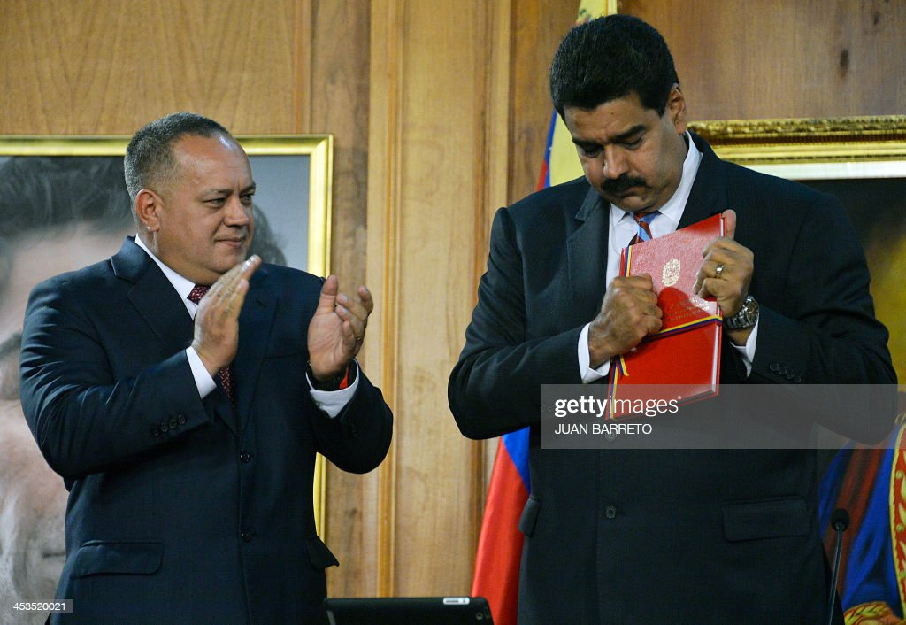 The president of the Venezuelan National Assembly, Diosdado Cabello (L), applauds after giving Venezuelan President Nicolas Maduro (R) the new law 'Plan de la Patria'--presented by the late president Hugo Chavez during the 2012 presidential campaign-- at the Miraflores presidential palace, in Caracas on December 4, 2013. AFP PHOTO/JUAN BARRETO
