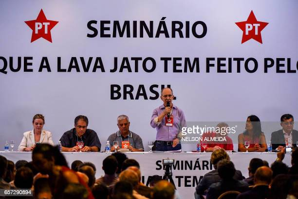 The president of the Workers Party Rui Falcao delivers a speech nex to former Brazilian president Luiz Inacio Lula da Silva and other participants...