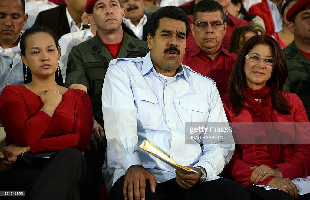 The President of Venezuela Nicolas Maduro (C), First Lady Cilia Flores (R) and the daugther of the late President Hugo Chavez, Rosa Virginia Chavez (L) attend a ceremony to commemorate Hugo Chavez's birthday anniversary, in Caracas, on July 28, 2013. AFP PHOTO/Juan Barreto