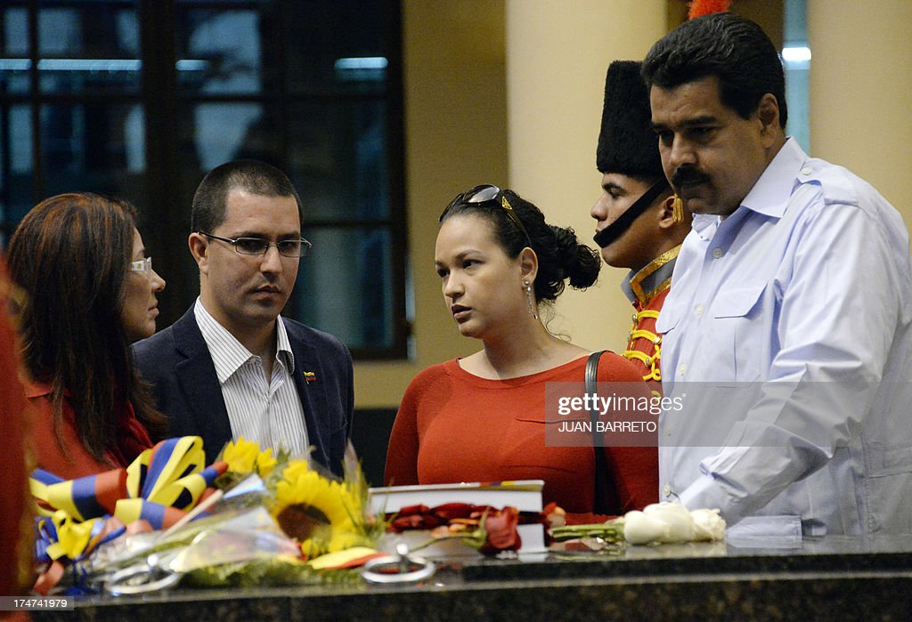 The President of Venezuela Nicolas Maduro (R) gestures next to (L to R) First Lady Cilia Flores, Venezuelan vice president Jorge Arreaza and his wife and daugther of the late President Hugo Chavez, Rosa Virginia Chavez during a ceremony to commemorate Chavez's birthday anniversary, in Caracas, on July 28, 2013. AFP PHOTO/Juan Barreto