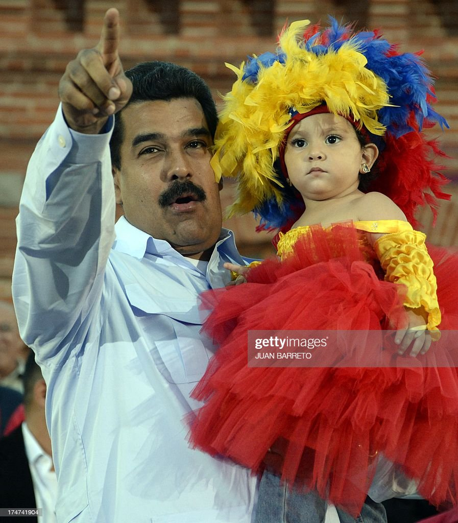 The President of Venezuela Nicolas Maduro holds a little girl during a ceremony to commemorate late president Hugo Chavez's birthday anniversary, in Caracas, on July 28, 2013. AFP PHOTO/Juan Barreto