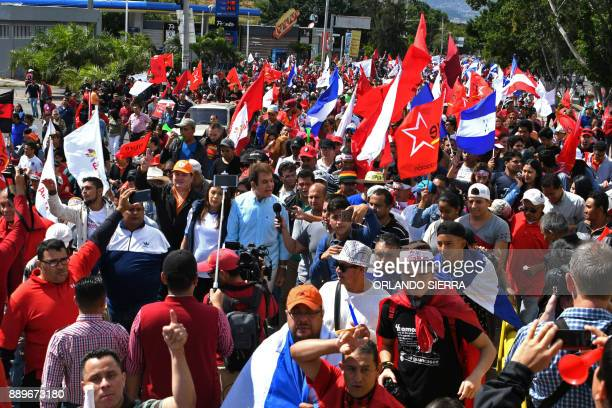 The presidential candidate for Honduras' Opposition Alliance against Dictatorship Salvador Nasralla talks to the press as he marches next to his wife...