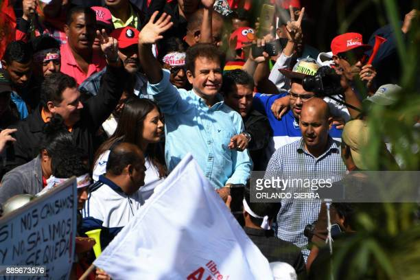The presidential candidate for Honduras' Opposition Alliance against Dictatorship Salvador Nasralla waves to supporters as he marches next to his...