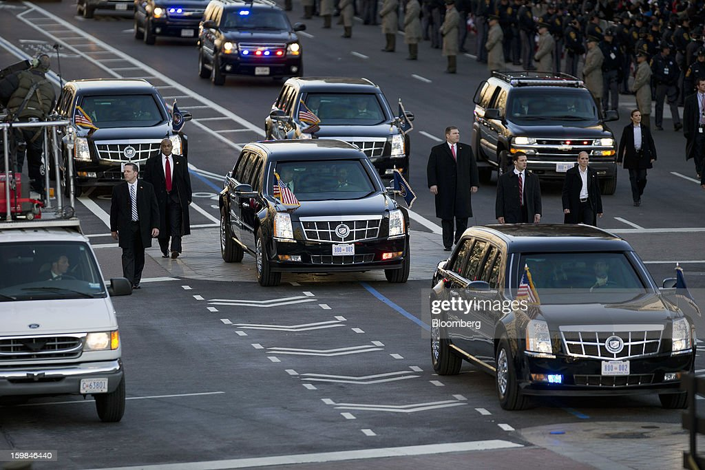 The presidential limousine, center, travels along the Pennsylvania Avenue parade route during the inauguration in Washington, D.C., U.S., on Monday, Jan. 21, 2013. A crowd estimated by police to be as large as 700,000, including warmly dressed women with American flags stuck in their hair, a smattering of celebrities and many Republicans, gathered today to witness President Barack Obama take his second oath of office on the steps of the U.S. Capitol. Photographer: Andrew Harrer/Bloomberg via Getty Images