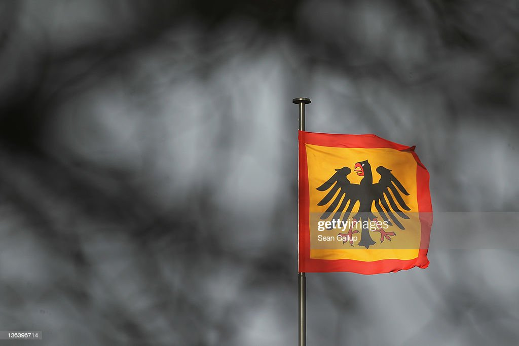 The Presidential standard, seen through the branches of a tree, flies over Schloss Bellevue presidential palace on January 4, 2012 in Berlin, Germany. German President Christian Wulff is coming under increasing pressure to resign following reports that he personally called Editor-in-Chief Kai Diekmann of Bild Zeitung and threatened him should the paper publish a story about Wulff's personal finance conduct while Wulff was prime minister of Lower Saxony.