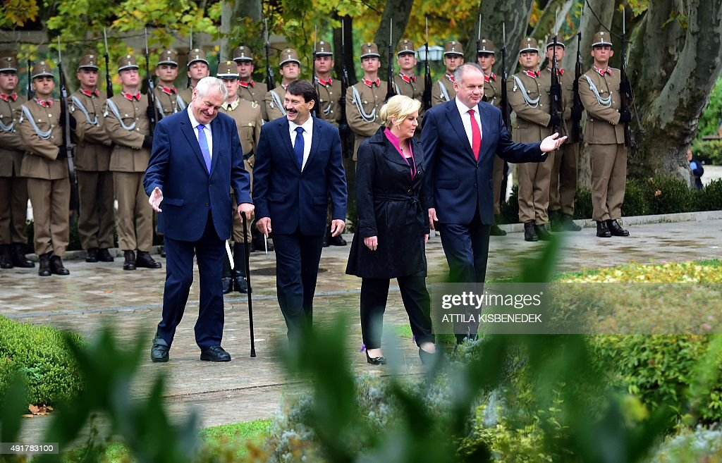 The Presidents of the Visegrad countries (V4) Milos Zeman (L) of the Czech Republic, Janos Ader (2nd L) of Hungary, Andrej Kiska (R) of Slovakia and the Croatian President Kolinda Grabar-Kitarovic (2nd R) talk after inspecting a military honor guard during an official welcoming ceremony in Balatonfured on October 8, 2015. Their talks are expected to focus on the migrants' situation, the climate change and the situation in the Western Balkans. The Polish President Andrzej Duda is expected to join the group later in the day. AFP PHOTO / ATTILA KISBENEDEK