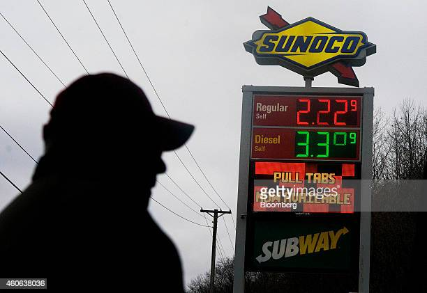 The price of regular unleaded and diesel fuels are displayed on a sign as the silhouette of a customer is seen at a Sunoco Inc gas station in...