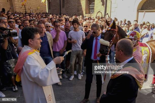 The priest celebrate the blessing of the horses ahead of today's Palio on August 16 2017 in Siena Italy The Palio is the most famous event in Siena...