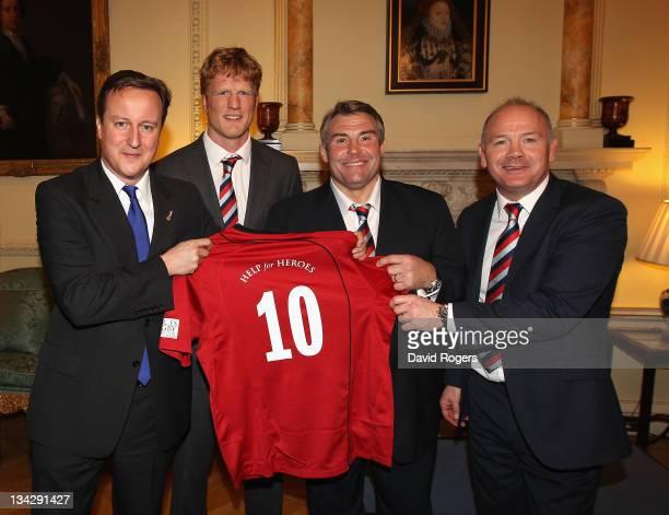 The Prime Minister David Cameron holds a Northern Hemisphere shirt with team captain Hugh Vyvyan and coaches Jason Leonard and Ieuan Evans during a...