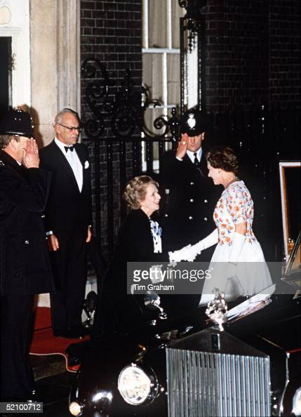 The Prime Minister Margaret Thatcher Curseying To The Queen At 10 Downing Street Her Husband Dennis Thatcher Is Standing Behind