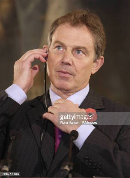 The Prime Minister Tony Blair listens over an earpiece to the simultaneous translation of a question from a Spanish journalist during a news...