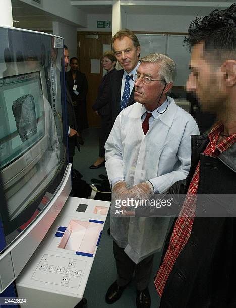 The Prime Minister Tony Blair looks on as an asylum seeker is finger printed 27 August 27 during his visit with the Home Secretary David Blunkett to...