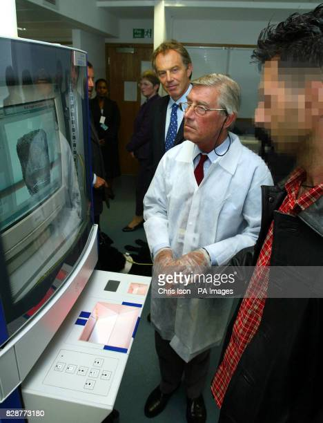 The Prime Minister Tony Blair looks on as an asylum seeker is finger printed during his visit with the Home Secretary David Blunkett to the asylum...