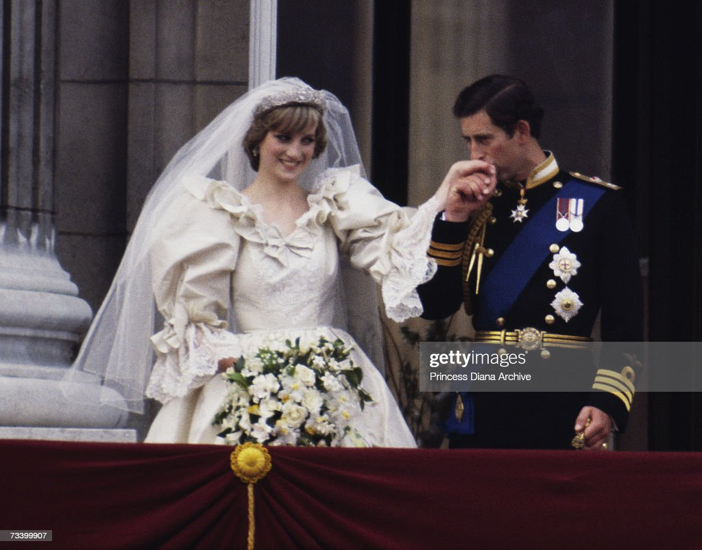 The Prince and Princess of Wales on the balcony of Buckingham Palace on their wedding day, 29th July 1981. She wears a wedding dress by David and Elizabeth Emmanuel and the Spencer family tiara.