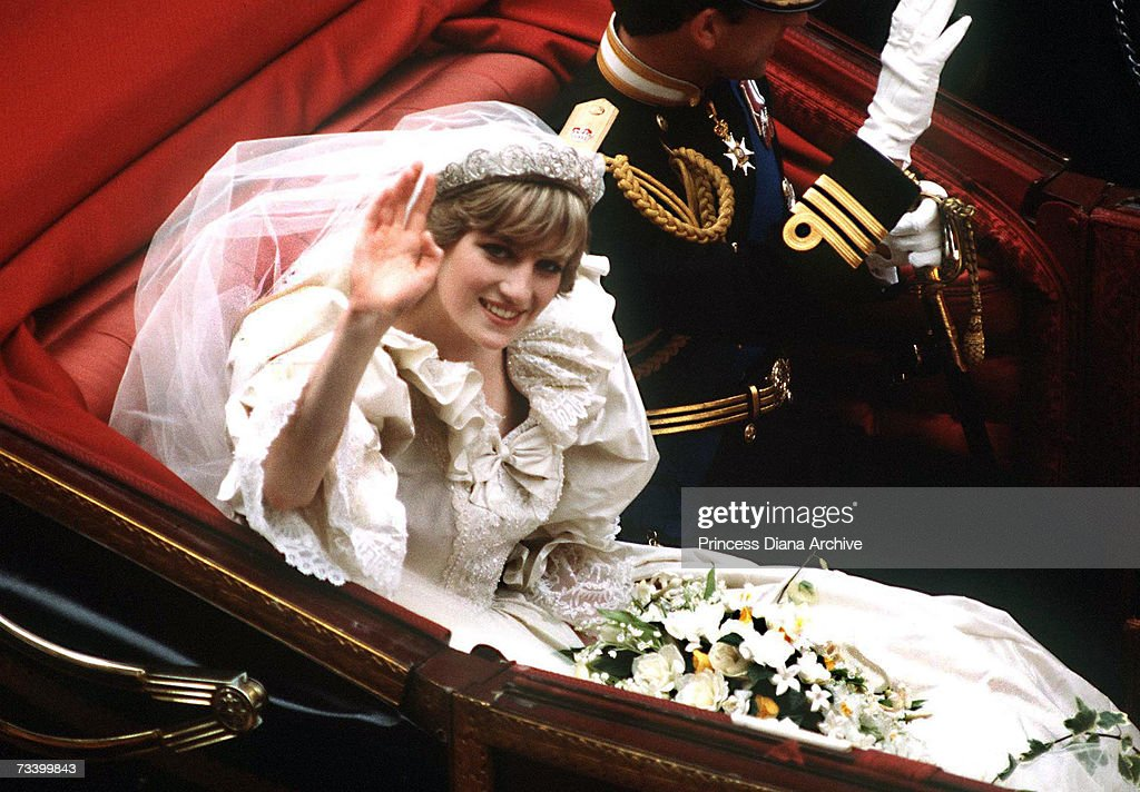The Prince and Princess of Wales return to Buckingham Palace by carriage after their wedding, 29th July 1981. She wears a wedding dress by David and Elizabeth Emmanuel and the Spencer family tiara.