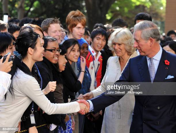 The Prince of Wales accompanied by the Duchess of Cornwall greet students after they arrive at the Keio University in central Tokyo this morning