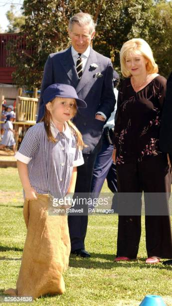 The Prince of Wales and headmistress Tracy Hammill watch Suzy Beers take part in a sack race at Coburg North primary school in the suburbs of...