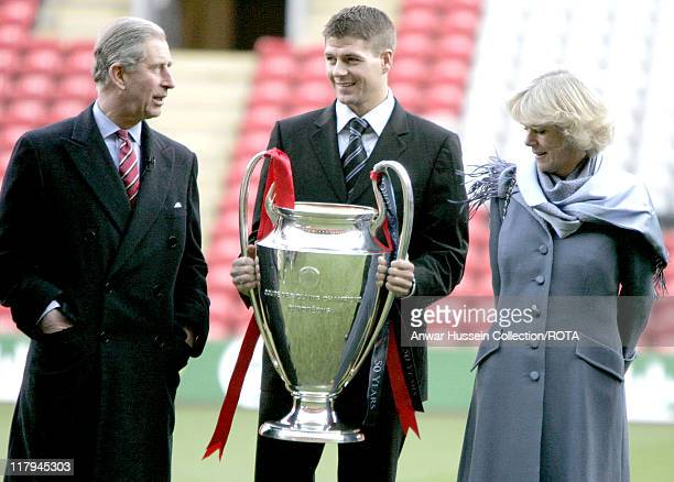 HRH The Prince of Wales and HRH Camilla Duchess of Cornwall with Liverpool captain Steven Gerrard holding the Champions League trophy during a visit...