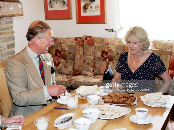 TRH The Prince of Wales and The Duchess of Cornwall enjoy tea and cakes when they visit Cwm Berem Farm Pontyberem Dyfed Tuesday July 12 2005 The...