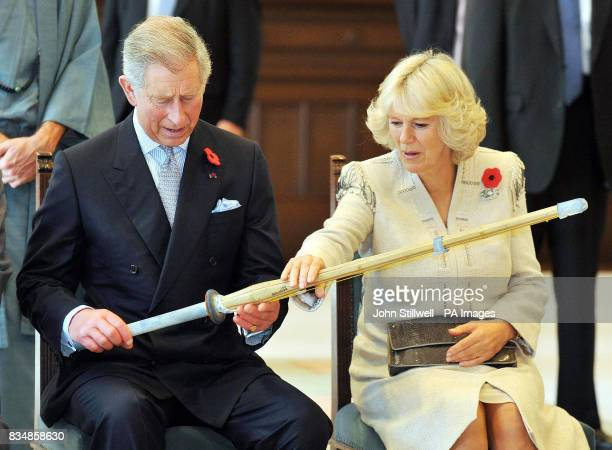 The Prince of Wales and the Duchess of Cornwall examine a Kendo practice bamboo sword after watch a Kendo sword demonstration at the Keio University...