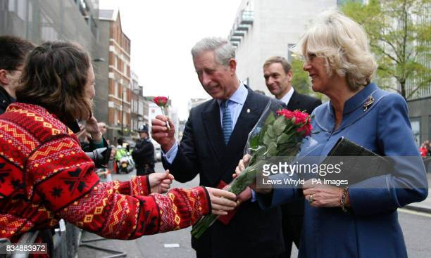 The Prince of Wales and the Duchess of Cornwall receive flowers from the public after leaving the Royal Opera House in London
