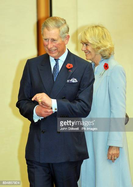 The Prince of Wales and the Duchess of Cornwall wait whilst Crown Prince Naruhito of Japan not in picture meets their staff after arriving at Haneda...