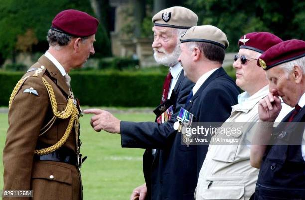 The Prince of Wales colonelinchief of the Parachute Regiment talks to Parachute Regiment veterans Lofty and Ken Cooper after presenting new Colours...