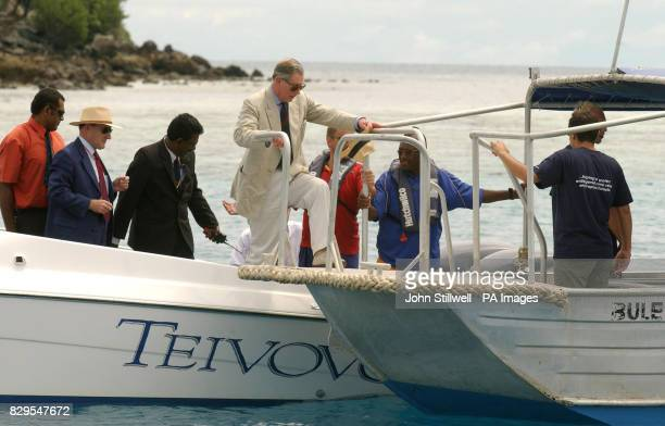 The Prince of Wales crossdecks from a speed boat to a glassbottomed boat to view scuba divers on a Coral Reef conservation project