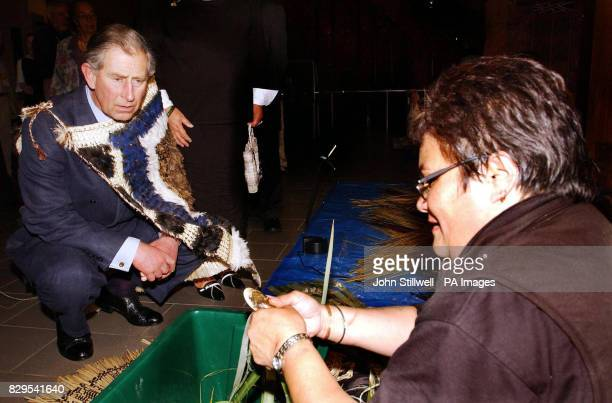 The Prince of Wales crouches and watches a weaver at work whilst wearing a Maori Korowai cloak during his tour of the Auckland War Museum in New...