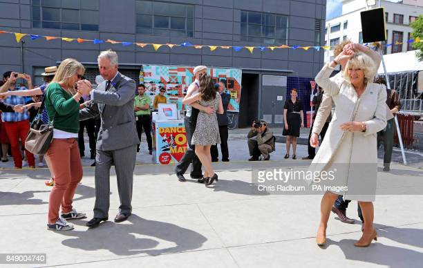 The Prince of Wales dances with Lisa Shannon whilst the Duchess of Cornwall dances with Sam Johnson from Christchurch during a visit to the Dance O...