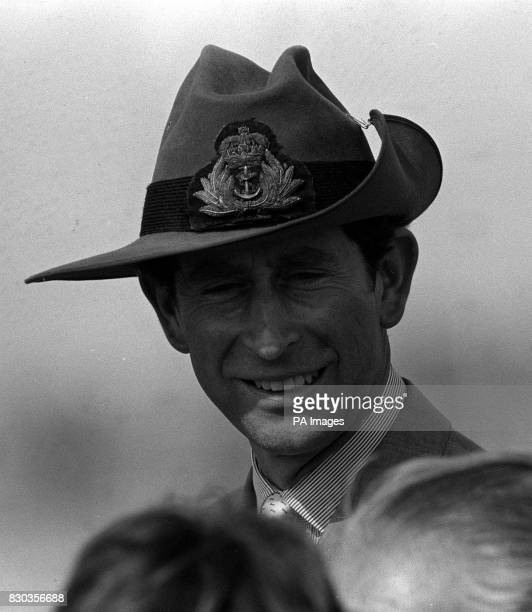 The Prince of Wales dons a borrowed 'digger's' hat to protect himself from the scorching sun as he smiles at the gathering on board HMS Cook after...
