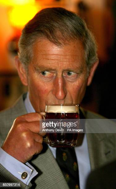 The Prince of Wales enjoys a drink in the Rising Sun Inn while touring the villages of Kingsand and Cawsand in Cornwall