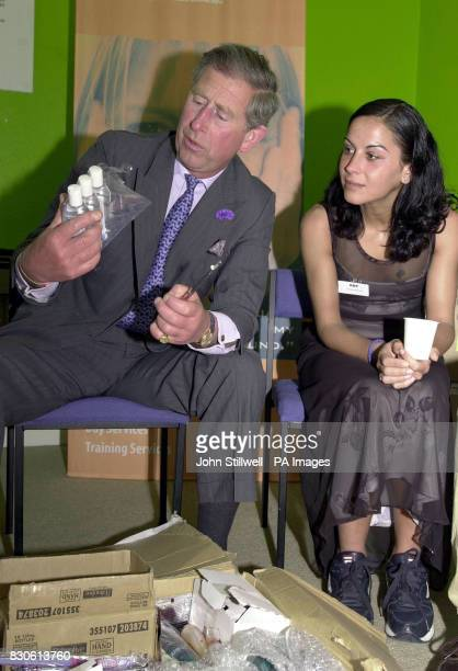 The Prince of Wales examines bottles of shampoo with Christina Martinez a resident at the Alcohol Recovery Project in Camberwell south London *The...