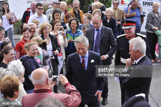 The Prince of Wales greets the crowds as he arrives at Canolfan Acapela a recording studio and concert venue in Pentref Wales