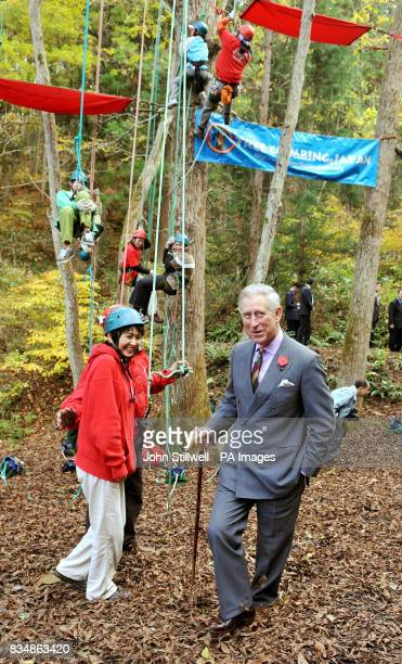 The Prince of Wales is amused by children climbing up trees during a visit to the Afan Forest near the village of Shinanomachi in central Japan