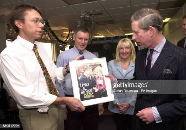 The Prince of Wales is presented with a front cover of the TV Times by Deputy Editor Roger Fulton which showed a photo of the Prince with the cast of...