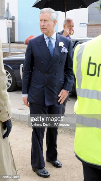 The Prince of Wales is seen with cement on his trousers after laying a thermoplan block during a visit to the Building Research Establishment...