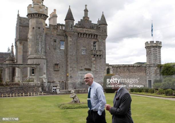The Prince of Wales known officially as the Duke of Rothesay when in Scotland talks to Head Gardener Billy Hughes during a visit to Abbotsford House...